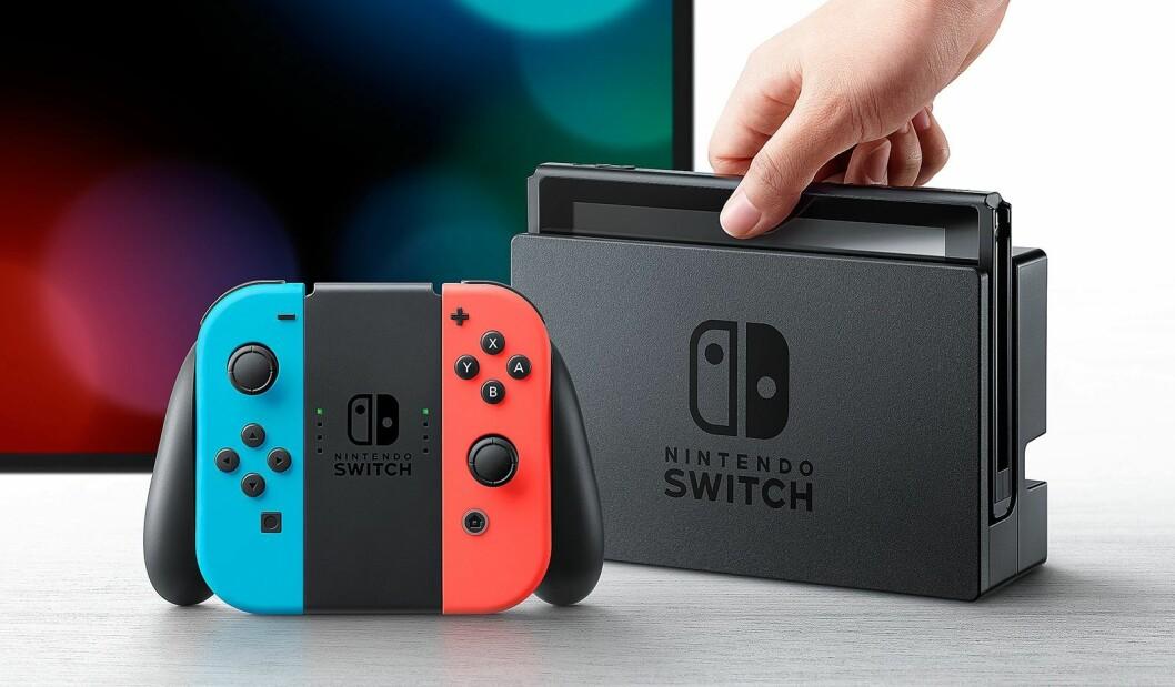 Nintendo Switch spillkonsoll med skjerm i ladestasjon, med to Joy-Con håndkontrollere satt i en Joy-Con Grip.
