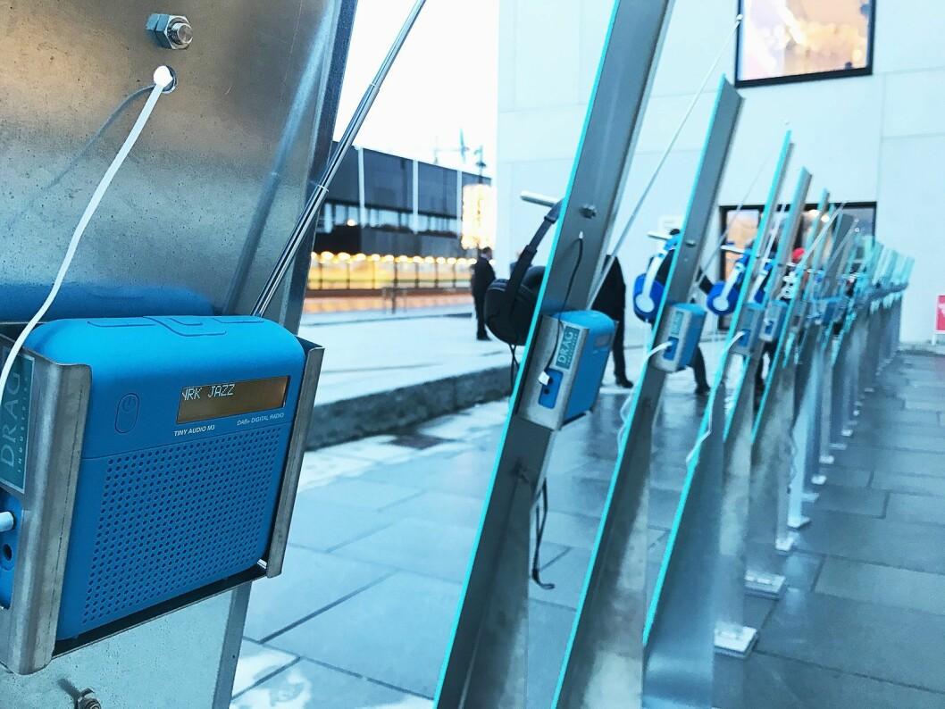 Utenfor kulturhuset i Bodø er det satt opp 28 Tiny Audio M3-radioer, der publikum kan lytte til de ulike dab-kanalene. Foto: Stian Sønsteng.