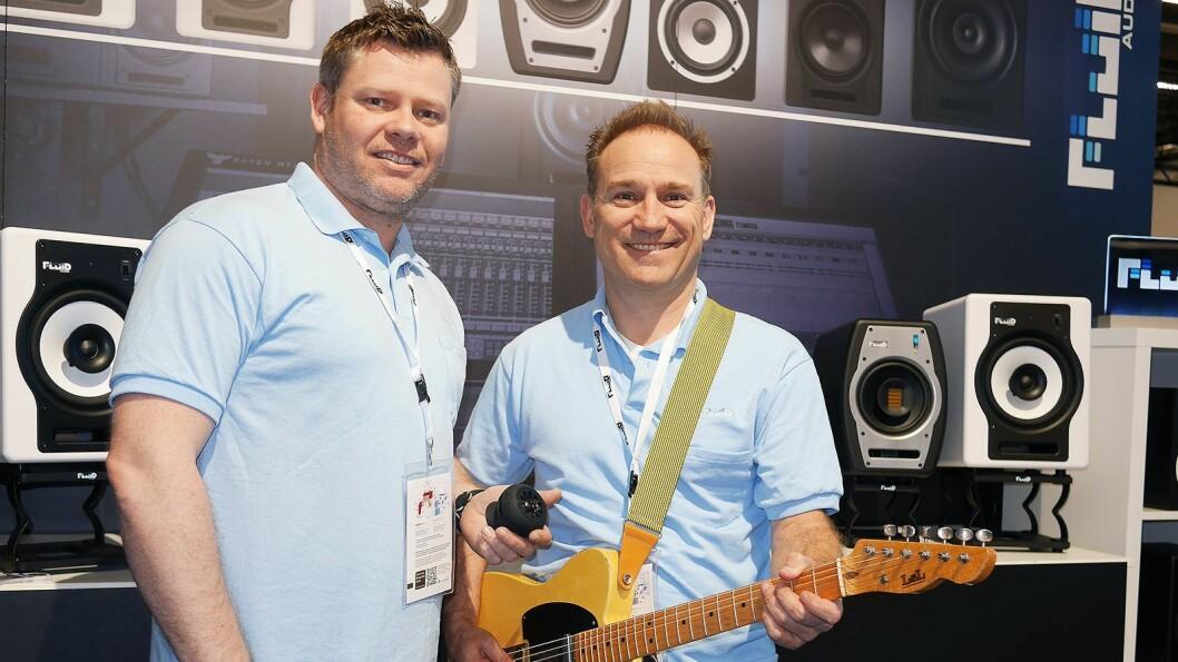 Kenneth Rustad (t. v.) og Kevin Zuccaro eier og driver Fluid Audio sammen. Her viser de gitarhøyttaleren Strum Buddy, i bakgrunnen noen av studiomonitorene og høyttalerstativene de leverer. Foto: Stian Sønsteng