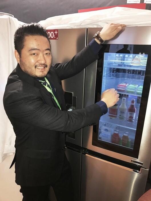 Robert Terøy, norsk salgssjef for husholdning i Elkjøp og Lefdal, banker på LGs smartskap GSX961NSAZ slik at innholdet vises gjennom skjermen.