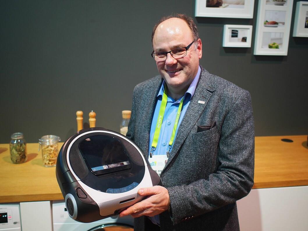 Stefan Finkbeiner i Bosch Sensortec viser frem en robotstøvsuger som er full av sensorer fra Bosch. Foto: Jan Røsholm