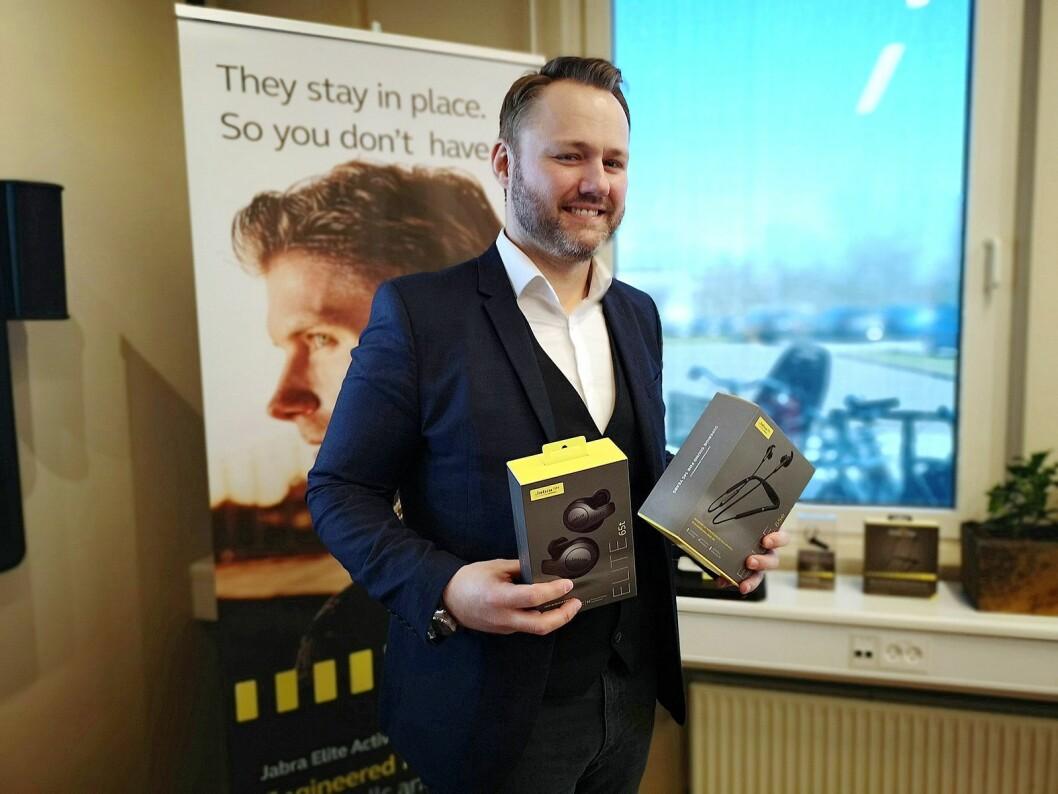 Nordisk salgssjef Steen Marquard viser fram Jabras populære trådløse øreplugger Jabra Elite 65t Active og ett av de nye proffsettene med nakkebøyle. Foto: Marte Ottemo