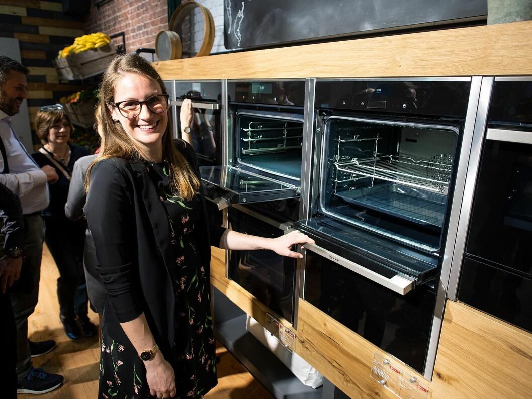 Miriam Neff i BSH med en ovn fra Neff med funksjonen Slide&Hide, der døren glir inn i ovnen når man åpner den. Foto: Ola Larsson