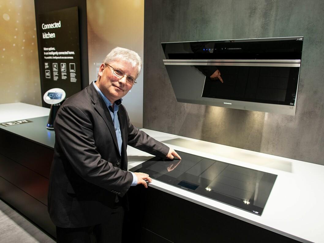 Joerg Voelkel i BSH med induksonstoppen og viften fra Siemens som er integrert i smarthjem-systemet Home Connect. Foto: Ola Larsson