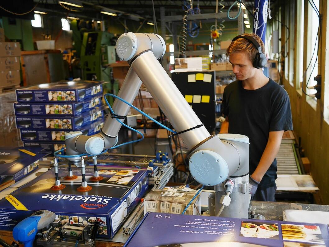 Håkon Kvernmoen med en kooperativ robot, som vasker og pakker de ferdige takkene. Foto: Stian Sønsteng.