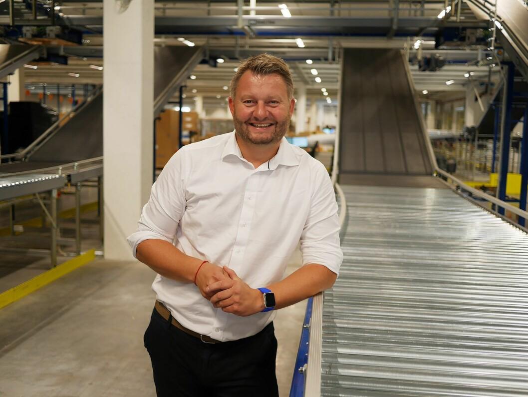 Logistikksjef Bjørn Tore Svendsen i Komplett-gruppen i første etasje i nybygget, ved sorteringsanlegget som brukes til den utgående varestrømmen. Foto: Stian Sønsteng