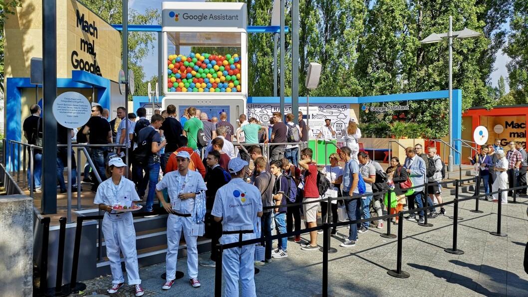 Hvitkledte Google-assistenter svarer på spørsmål fra publikum og deler ut frukt. Foto: Marte Ottemo.