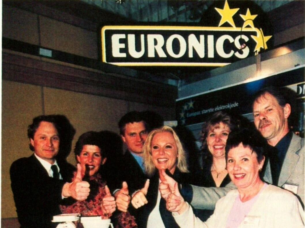 Administrasjonen i Euronics Norge i 2001 med den nye logoen. F. v. Kenneth Baltzersen, Solgunn Øvereng, Asle Bjerkebakke, Anne Line Svendsen, Kari Ann Jensen, Gunni Hansen og Terje Gudmundsen. Foto: Erik Andersen.