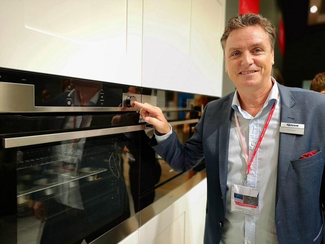 Ragnar Eknes, salgssjef hos Gram i Norge, viser fram en ny ovn med trykkfølsom dør og større ovnsrom. Foto: Marte Ottemo