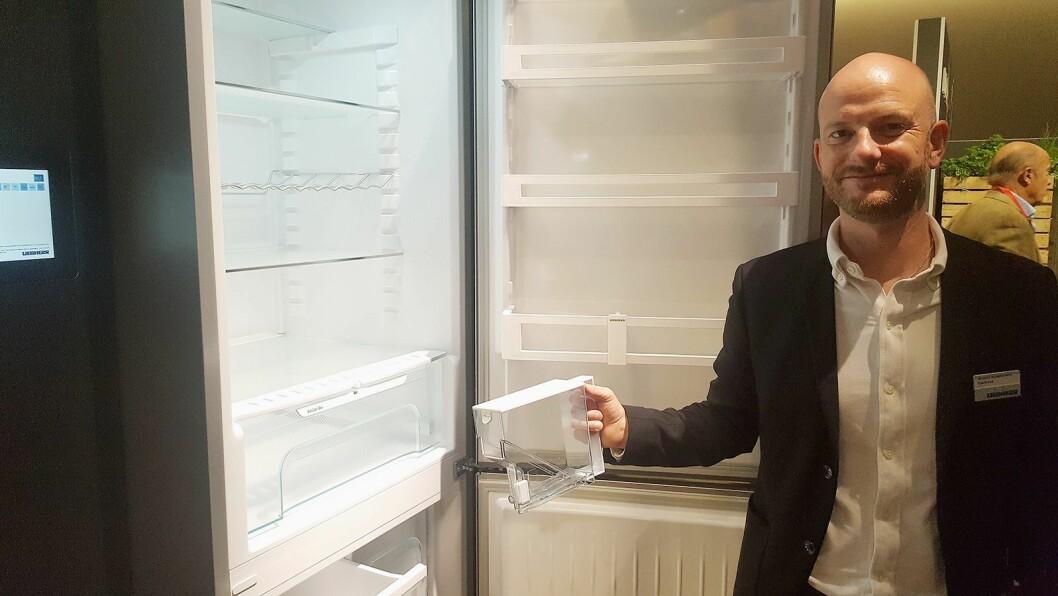 Anders Rosenkrans Gjedsted viser frem den integrerte vanntanken i Liebherr kjøleskapet. Foto: Cathrine Pedersen.