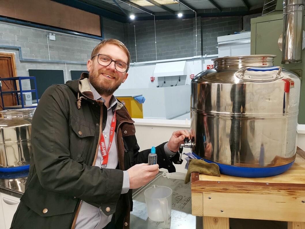 Eksportsjef Phil Harrop med beholderen der ventiloljen av merket Champion blandes. Foto: Stian Sønsteng.