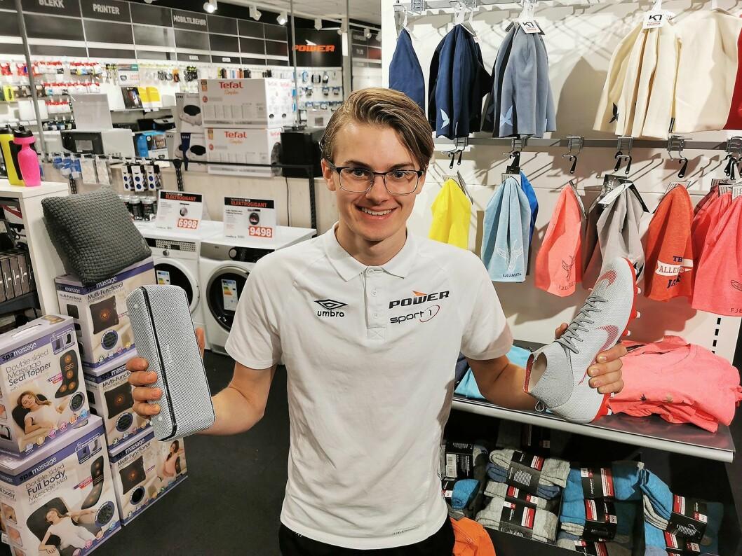 Butikksjef John Fredrik Nelvik i El & Sport AS på Smøla har to logoer på trøya, og håndterer både sport og elektronikk med Sport 1 og Power i samme butikk. Foto: Stian Sønsteng