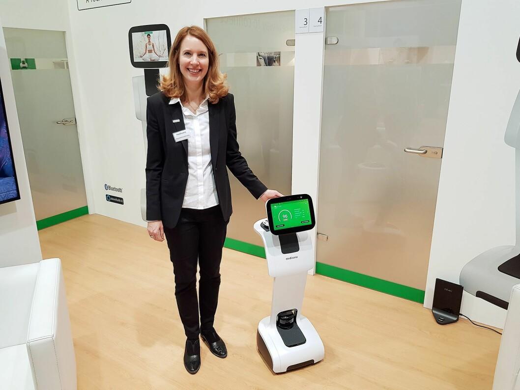 Anja Schimmelpfenning fra Medisana viser frem Homecare Robot. Legg merke til basestasjonen nede i høyre hjørne. Foto: Jan Røsholm.