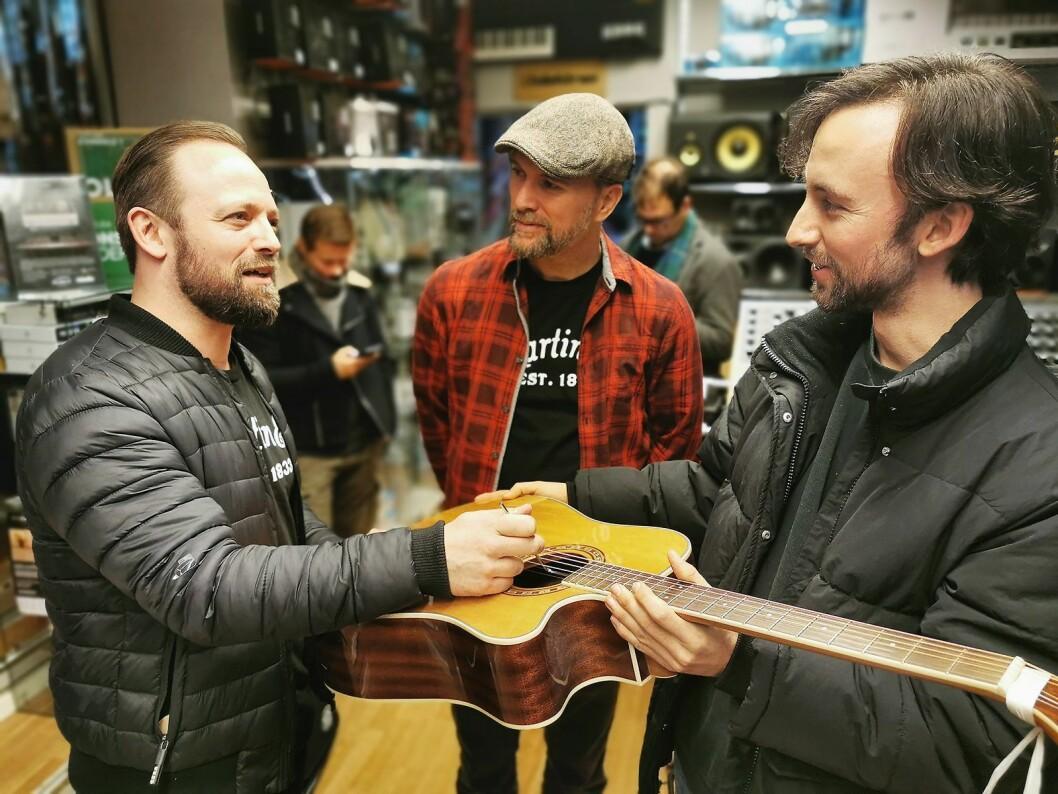 Mats A. Haugen (f. v.) og Øyvind Voldmo Larsen hjelper kunde Jørgen Hamran med å justere gitaren hans. Foto: Stian Sønsteng.