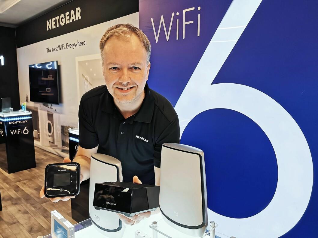 Norden-sjef Pål Vatneberg i Netgear med 5G (t. v.) og Nighthawk-ruterne i hendene, samt de hvite Orbi-ruterne. Alle har Wi-Fi 6, de to siste også maskenettverk (mesh). Foto: Stian Sønsteng