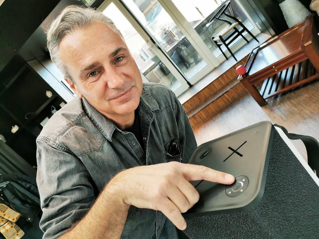Doug Ebert viser de fire knappene som gjøre det mulig å sømløst velge mellom to blåtannenheter, én 3,5 mm inngang og én optisk inngang. Foto: Stian Sønsteng.