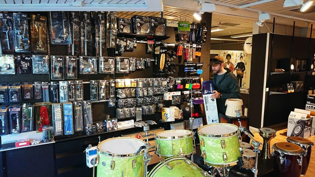 Butikksjef og medeier Andreas Jentoft i Lydproduksjon Tromsø setter nye varer på plass i den nye butikken. Foto: Eirik Haua