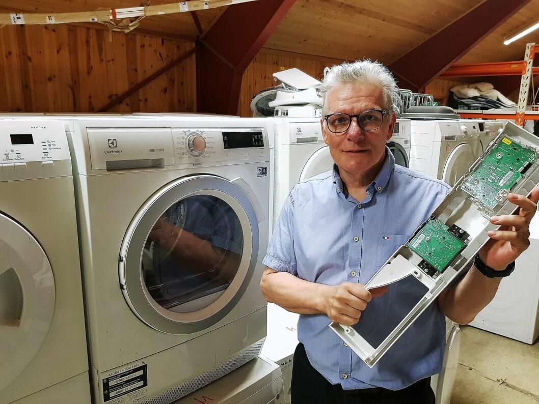 Tommy Paulsen med et styringskort til en vaskemaskin, en modul de ofte bytter. Foto: Jan Røsholm