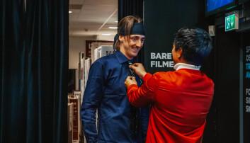 NRK-programleder Christian Strand hjelper TIX (Andreas Andresen Haukeland) med slipset på bakrommet ved Elkjøp Slependen. Foto: Sløsesjokket/NRK